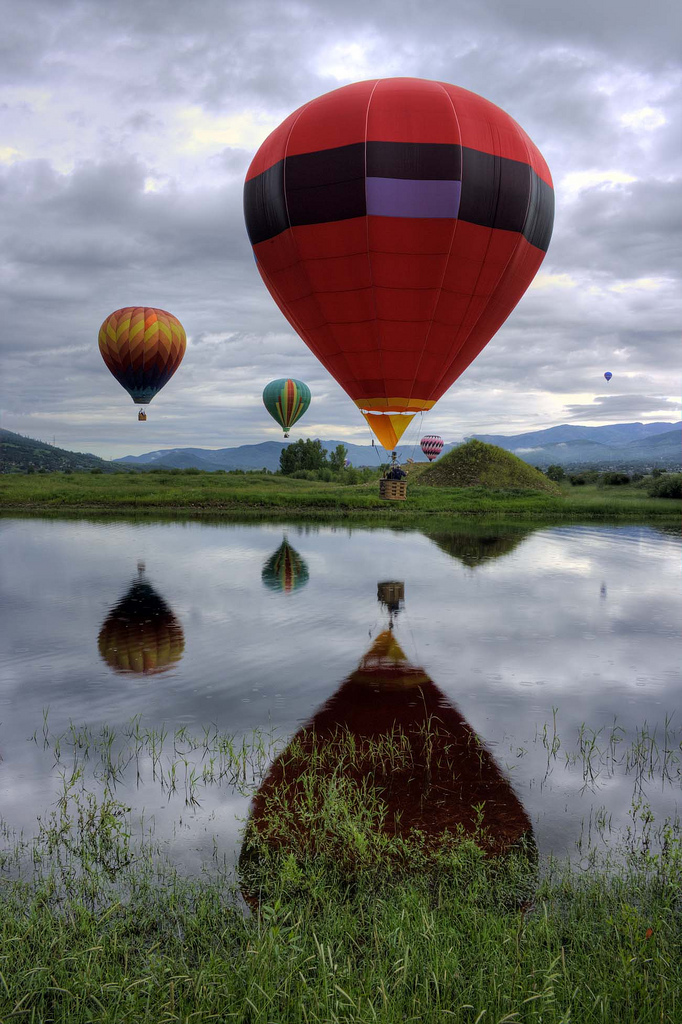 three Hot Air Balloons reflected on a pond