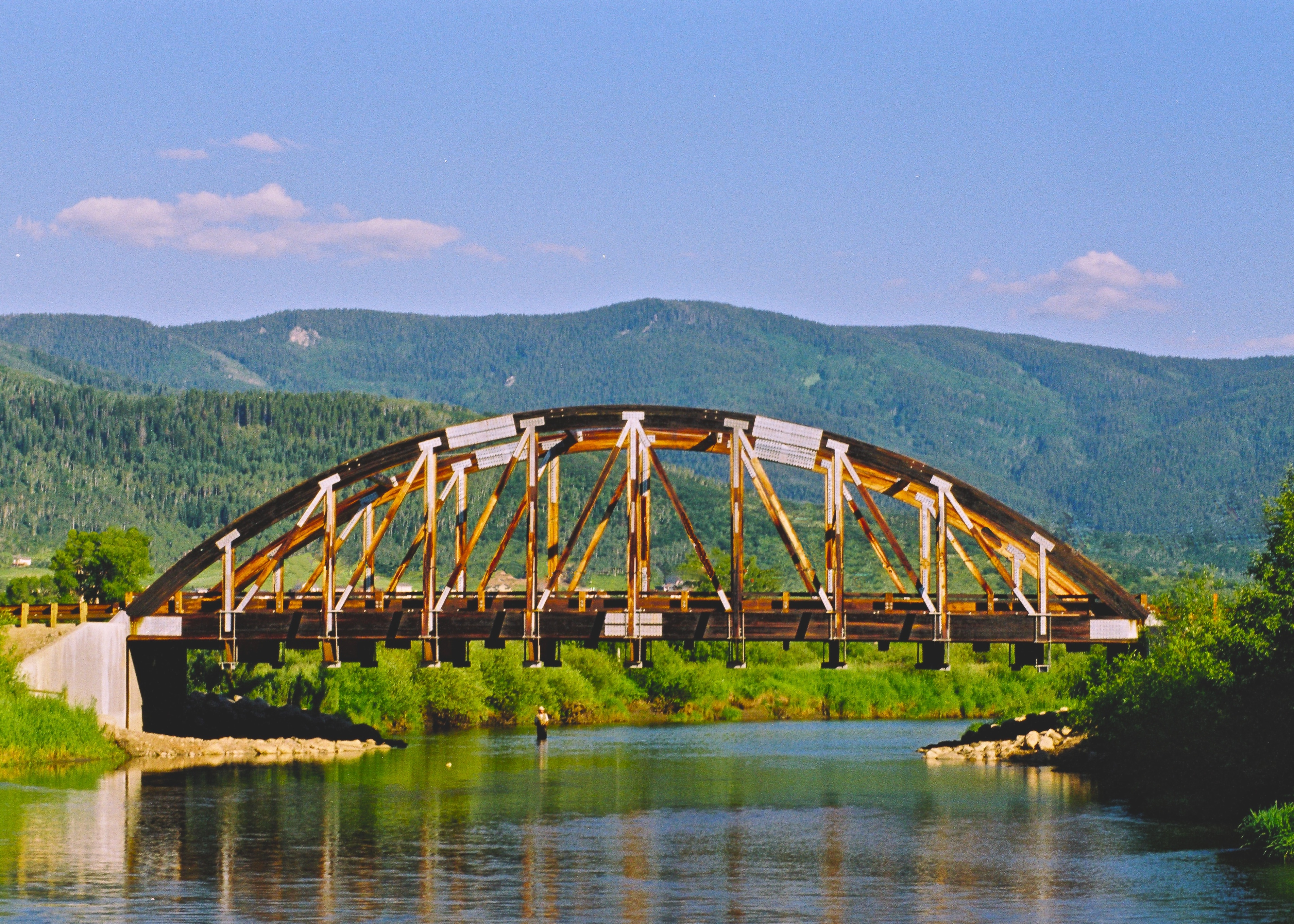 bridge over yampa river with fisherman in background
